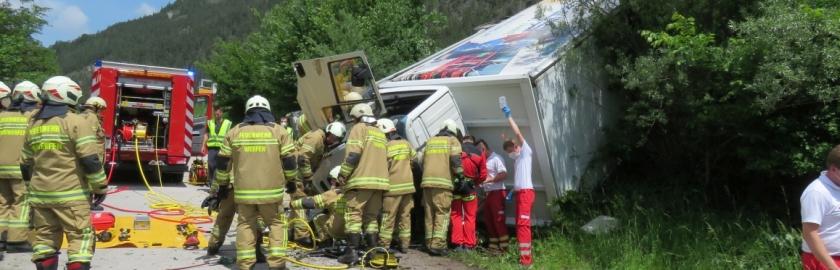 LKW durchbricht Leitschiene, Fahrer eingeklemmt